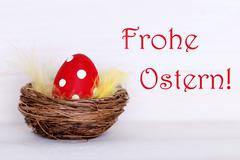 One Red Easter Egg In Nest With German Frohe Ostern Means Happy Easter - stock photo