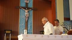 Sacristan assists priest vestment - stock footage
