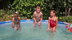 Happy boy and two girls spritz in swimming pool in garden Stock Footage