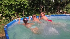 Happy boy and two girls splash by legs in swimming pool in garden Stock Footage