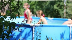 Three happy children play in swimming pool in summer garden Stock Footage