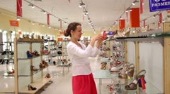 Beautiful young woman chooses shoes in one of shops at complex Stock Footage