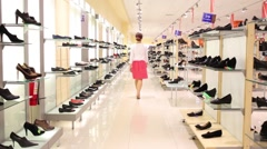 Back of young woman looking at shoes in big modern shop. Stock Footage