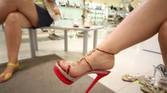 Legs of two women trying on shoes in big shoes store Stock Footage