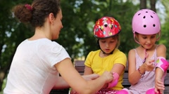 Woman helps two girls put on protective knee and elbow pads Stock Footage
