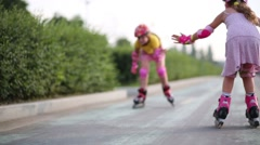 Two girls in roller skates, knee and elbow pads ride on rollers Stock Footage