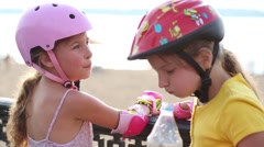 Two girls in protective pads and helmets drink water Stock Footage