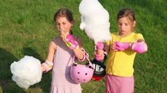Two girls with helmets eating candy-floss on green grass outdoor Stock Footage