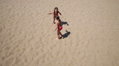 Two little girls play catch up on yellow sand of beach Stock Footage