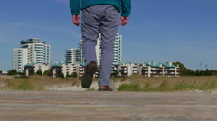 A Man Walks by a Wooden Walkway to Town Stock Footage