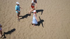Woman with three happy children play blindman buff on sand Stock Footage