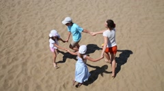 Woman with children run around in circle holding hands on sand Stock Footage