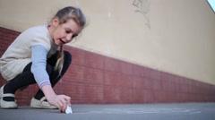 Little girl draws hopscotch on asphalt by white chalk on street - stock footage