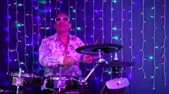 Bald smiling man in sunglasses plays drum set in night club Stock Footage