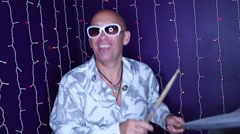 Happy bald man in sunglasses plays drum set in night club Stock Footage