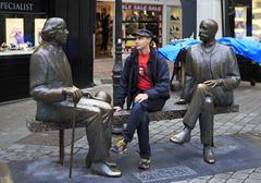 Tourist on the bench with Irish writer Oscar Wilde - stock photo