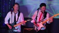 Two guitarists perform on stage with illumination in night club Stock Footage