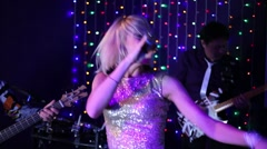 Musical group of two men and woman performs on stage in club Stock Footage