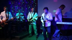 Group of five musicians with saxophone perform on show in club Stock Footage