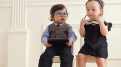 Baby boy with tablet computer sits on chair next to baby girl Stock Footage