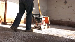 Stock Video Footage of building construction workers flattening hardcore floor with vibration plate