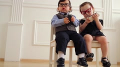 Baby boy and baby girl in glasses sit with mobile phones - stock footage