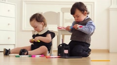 Baby boy and baby girl sit on floor with colored markers Stock Footage