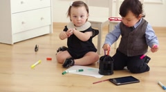 Baby boy and baby girl sit on floor play with colored markers Stock Footage