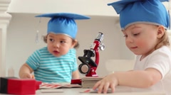 Babies in blue graduation hats play with microscope on table Stock Footage