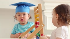 Two cute babies in blue graduation hat play with abacus on table Stock Footage