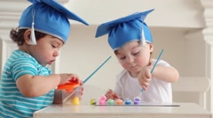 Two cute babies in blue graduation hats paint colors Stock Footage