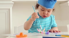 Two cute baby boy in blue graduation hat paints colors on table Stock Footage