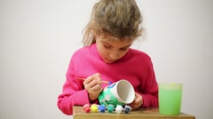 Little cute happy girl in pink wear paints white cup Stock Footage
