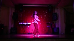 Young woman in red costume with drum dances belly dance on stage Stock Footage