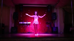 Pretty young woman in red costume dances belly dance on stage Stock Footage