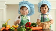 Two babies in kitchen aprons and caps stand near table Stock Footage