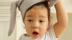 Cute baby boy removes hat with ears of rabbits in white room Stock Footage