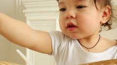 Cute baby boy pulls spoon out of basket in white room Stock Footage