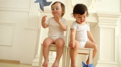 Cute baby boy and girl with toy windmills sit on wooden chairs Stock Footage