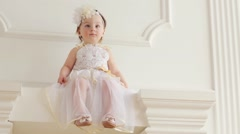 Cute baby girl in costume of bride sits on decorative fireplace Stock Footage