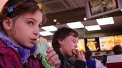 Boy and girl have snack at restaurant KFC in Moscow. Stock Footage