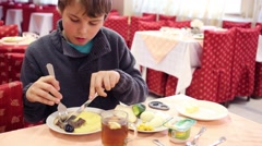 Boy eating meat and mashed potatoes with knife and fork Stock Footage