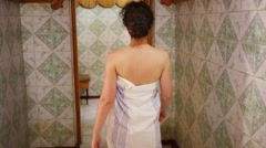 Back of young woman wrapped in sheet entering in spacious sauna Stock Footage