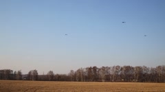 Three black helicopters fly in sky above field with dry grass Stock Footage