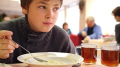 Handsome boy eats porridge in canteen with red chairs Stock Footage