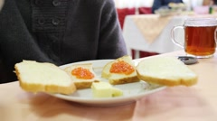 Sandwiches with red caviar and butter on plate and cup of tea Stock Footage