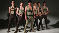 Stock Video Footage of Group of six young men in costumes poses during photo session