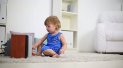 Cute kid in blue touches stereo system on carpet in room Stock Footage