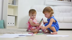 Two little cute girls paint pencils on floor in room at home - stock footage