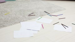Many pencils and paper sheets with kids draws on floor in room Stock Footage